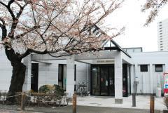 桜の大木に守られるように立つ管理事務所