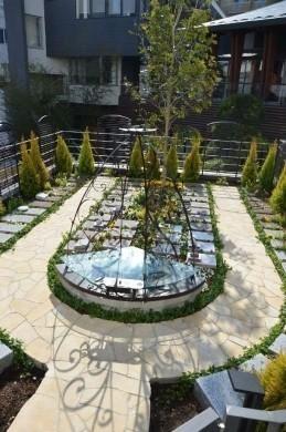 本堂よりも入口近くにある永代供養納骨堂。フェンス沿いには観葉植物のゴールドクレスト、墓石のまわりにはツル科植物のヘデラ・ピッツバーグが植えられている。