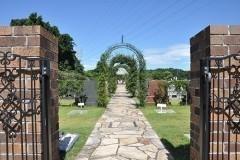 墓苑のエントランス。みずみずしいグリーンに縁どられた石畳の中央通路。フラワーアーチの奥には純白のガゼボ。