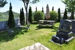 噴水がある芝生区画にさりげなく置かれたテント付きの木製テーブルと鋳鉄のベンチセット。遠景には保土ヶ谷の丘陵。ここでのランチは心地よさそう!